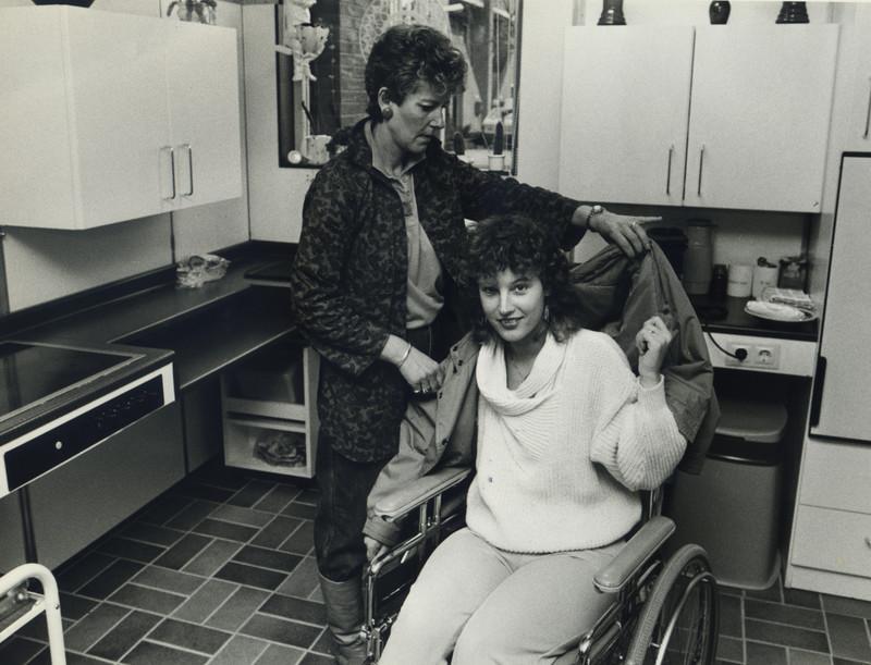 foto uit 1980 van meisje in rolstoel dat geholpen wordt met ADL